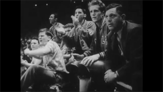 1940s: Players on bench watch game. Men play basketball. Men on sidelines cheer.