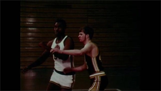 1970s: Basketball players push and shove one another on court. Referee blows whistle and waves arms.