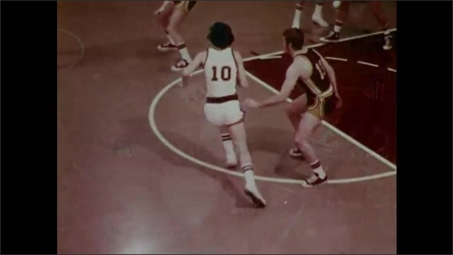 1970s: Men slam into one another and fall on court in slow motion. Players screen and guard one another on basketball court.