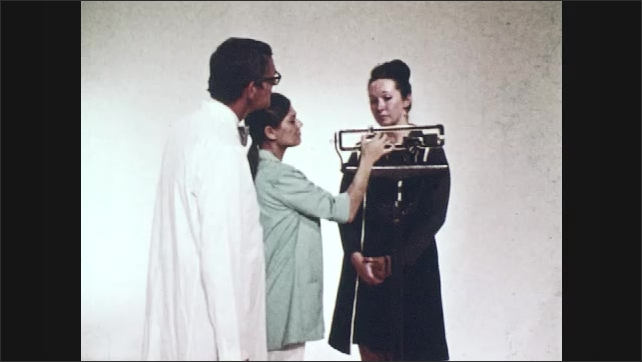 1970s: UNITED STATES: man in white coat. Man hops up and down on leg. Nurse talks to man. Lady on scales. Nurse winks at doctor. Doctor speaks to camera