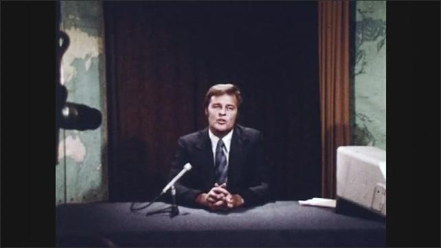 1970s: UNITED STATES: man hosts show Man looks at camera. Man in film studio