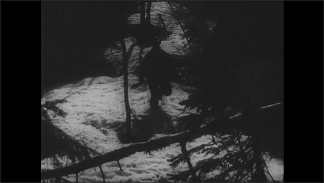 1950s: Man and dog run down mountain. Man trips over log, falls, rolls down hill.