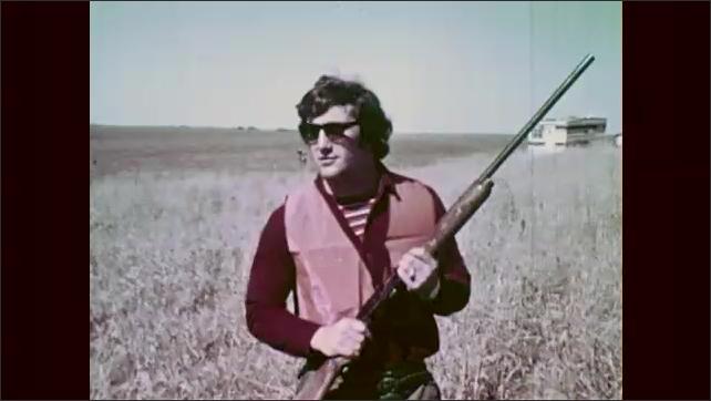 1960s: Men hold guns, walk through field. Men stand in field. Dog stands in field.