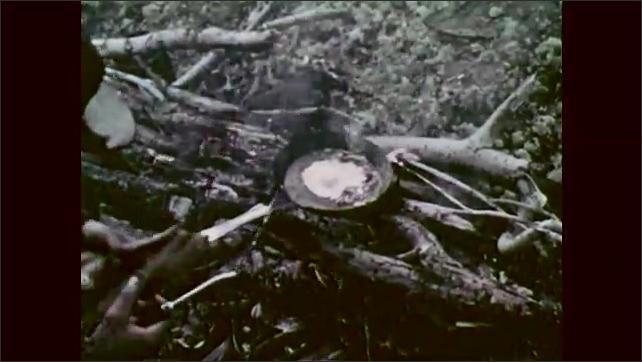 1960s: Men cook food on campfire. Men pour drinks, serve food.