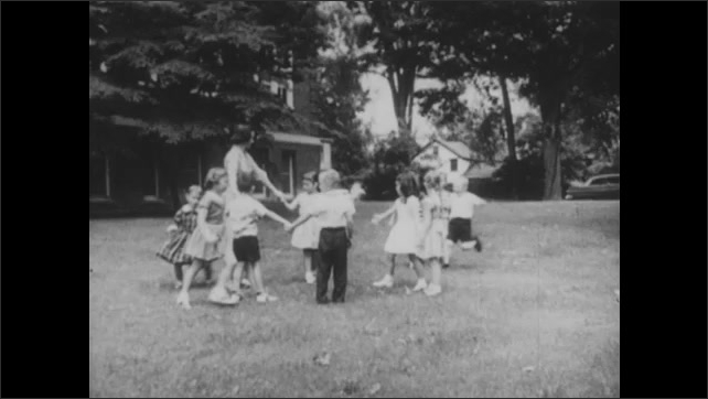 1950s: UNITED STATES: boy watches class from corner. Recess time at school. Children hold hands in circle. Children exclude boy  from games.
