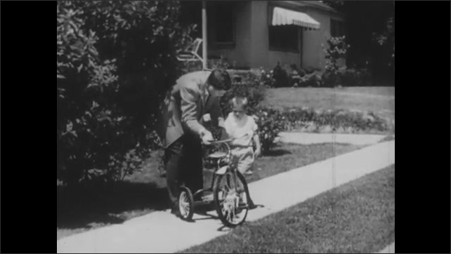 1950s: UNITED STATES: man tells boy off. Man takes bike from boy. Girl watches boy get reprimanded. Boy watches children on bikes from window