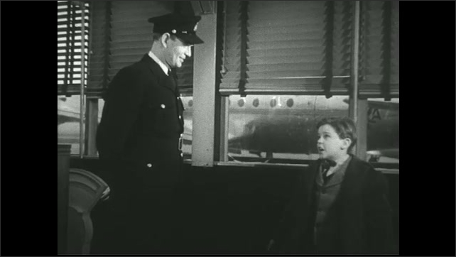 UNITED STATES 1940s  ?????Pilot talks to young boy seated in  airport terminal.