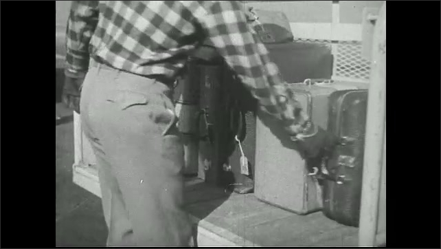 UNITED STATES 1940s  ????? American Airlines is filled with gas. Men place luggage on conveyor belt into plane.