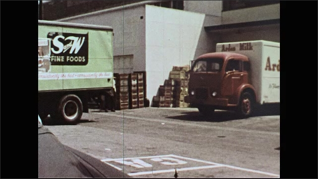UNITED STATES 1950s: Man and boy open delivery door, man points / Truck backs up / Man and boy on loading dock.