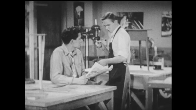 1950s: Two teenage boys in high school shop classroom are talking while one of them holds a newspaper.