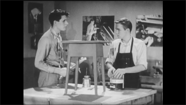 1950s: Two teenage boys in high school shop classroom have a conversation while one holds newspaper and the other takes apron off.