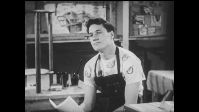 1950s: Teenage boy sits alone in shop class, holding papers and nodding to himself, thinking.