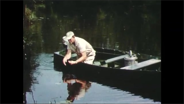 1950s: flies move across dead fish floating on surface of water. man in hat smokes cigarette, reaches over boat and pulls up line to bring up giant cage from pond in countryside.