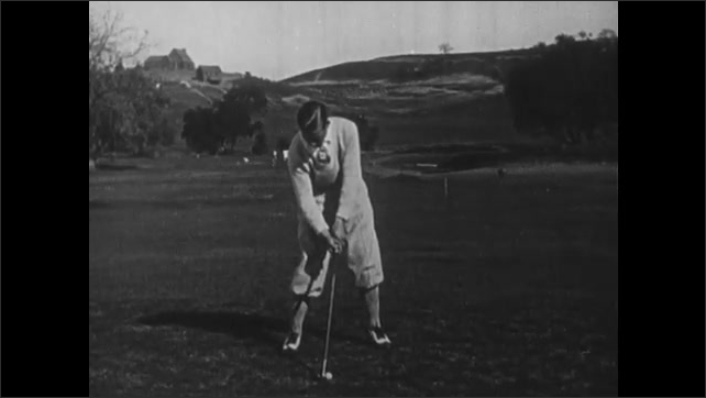 1930s: Golf course.  Man swings and hits golf ball.