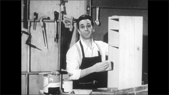 1950s: Man in workshop sands bookshelf. Man stops work and speaks. Man continues sanding.