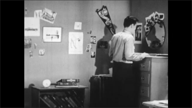 1950s: Boy nods and speaks while sitting on bed. Boy walks across room to dresser and speaks. Boy opens drawers and looks for something.