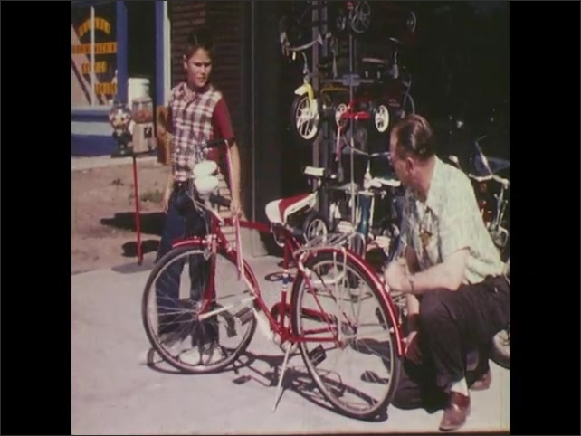 1960s: Rubber balloon tire. Schwinn Wasp chain guard. Boy looks at red Schwinn bike with bicycle shop owner and touches handlebar streamers. Boy bikes off down the sidewalk.