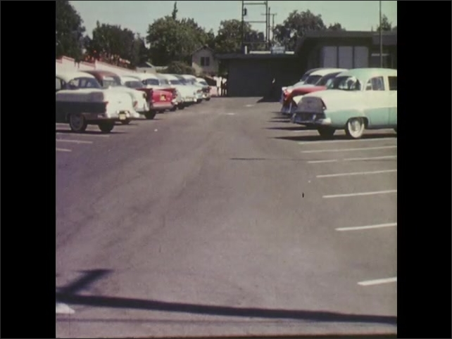 1960s: Teenage boy bikes into hospital parking lot. Teenage boy enters hospital through door.