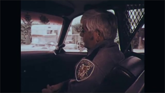 1970s: Two policemen in car talk and drive. Cyclist in lane ahead of policemen makes slow signal and turns right in intersection.