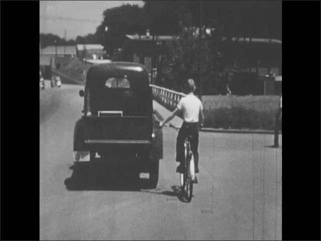 1950s: Boy holds onto back of truck while on bicycle. Words never do this.