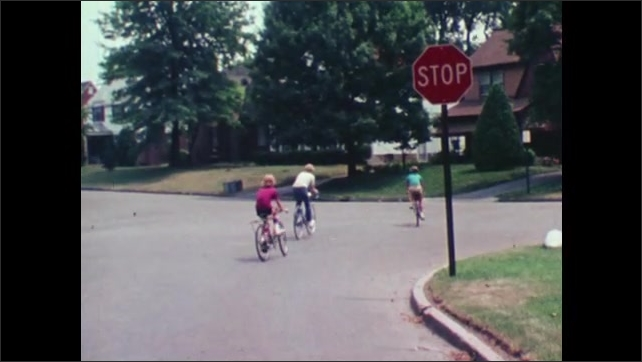 1980s: Boy smiles. Three kids sit on bicycles next to stop sign. Kids on bikes ride down road, car turns after them.