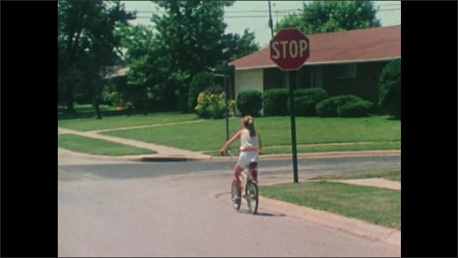 1980s: Turn signal blinks on car. Man drives car. Looking at sideview mirror on car while driving. Girl rides bike to stop sign, using hand signal. Girl looks both ways then rides down road.