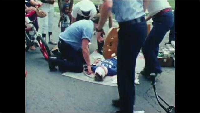 1980s: Medics attend to boy lying on ground with blood around him. Boy on bike watches. Medics put boy on stretcher. Crowd watches.