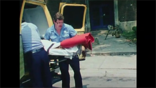 1980s: Medics lift boy on stretcher from road and put him in back of ambulance then shut ambulance doors.