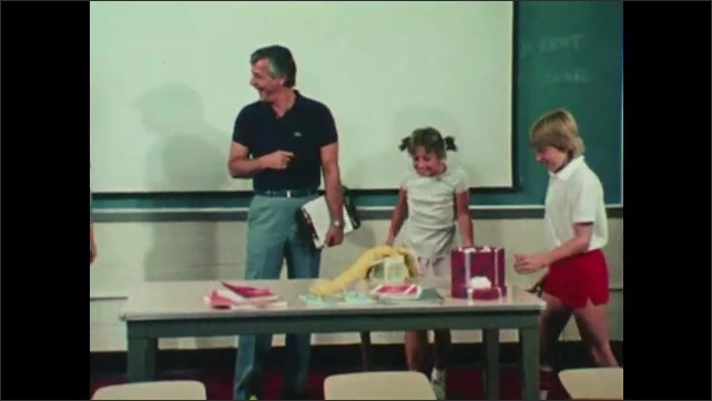 1980s: Girl in classroom talks and stands up. Three students in classroom approach table in front. Girl opens box. Man and boy stand back. Fake snakes spring from box when girl opens it.