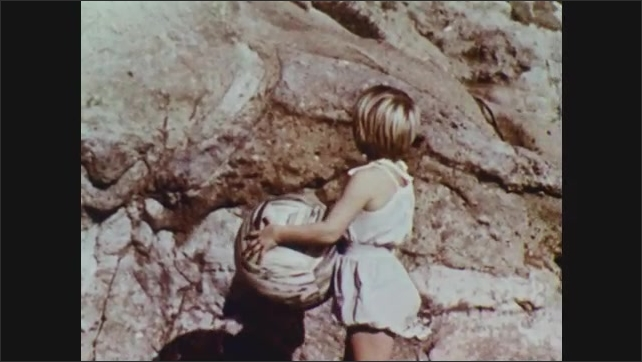 1960s: young girl holding a large ball looking around at large rocky outpost on beach