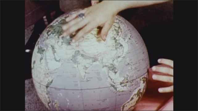 1960s: father and child spinning globe around and then pointing at Los Angeles