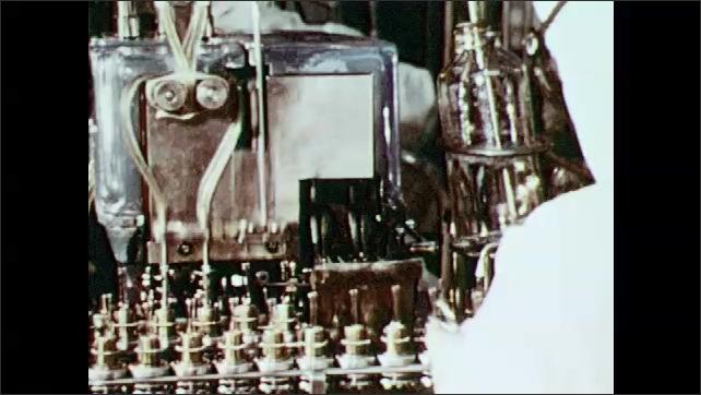 1980s: People work in a factory, filling medicine bottles.