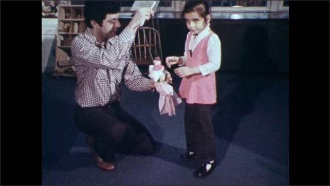 1970s: Puppet with speech bubble behind it on board. Man in classroom guides blind girl who conducts puppet into motion. Girl feels puppet as man holds puppet.