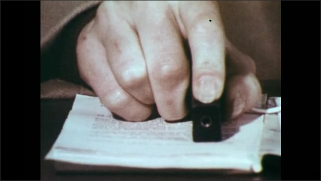 1970s: Woman sits at desk, scans paper with optacon reading device, finger guides apparatus over page. Machine on table. Woman concentrates, blinks.