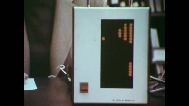1970s: Hand scans paper with apparatus. Light display of dotted code, woman at desk scans page beyond screen.