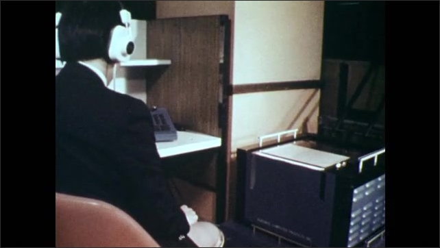 1970s: Man at desk wears headphones, turns knobs on machine next to optical scanner. Scanner scans as man types on machine. Switches and buttons on translating machine.