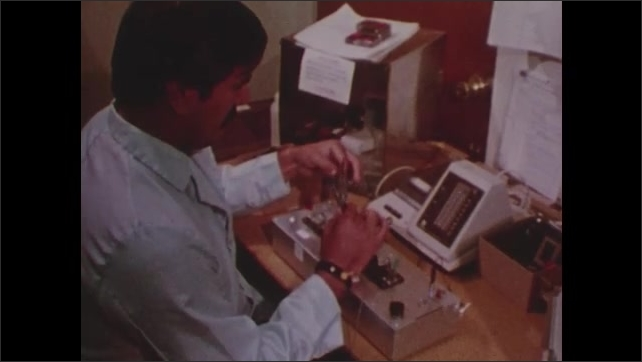 1970s: View of object turning inside lab machine. View of lab computer screen. Worker plugs wire into wristband, presses buttons on lab equipment. View of hospital sign zooms into building