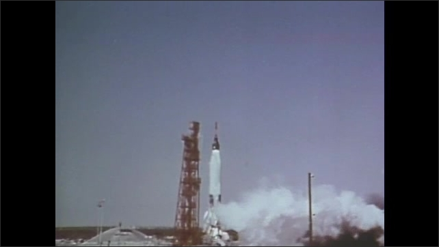 1960s: People stand in a line behind cameras on tripods. Space rocket takes off. Astronaut sits in space rocket.