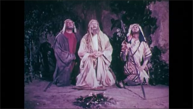 1950s: UNITED STATES: shepherds sit by fire. View of stars in sky. Angel speaks to shepherds.