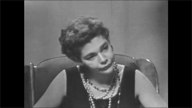 1950s: Man in white t-shirt talks dramatically, looks sad. Woman with beaded necklace sitting in chair responds, angry.