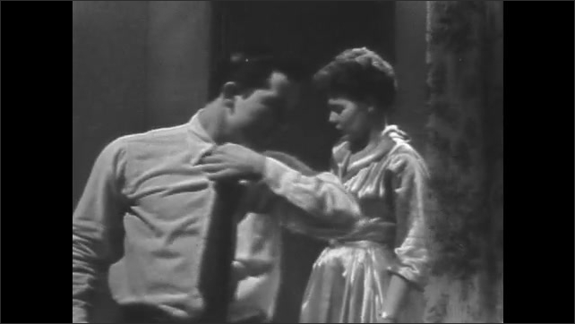 1950s: Woman in nightgown stands up from table and opens door, man in shirt and tie enters room. Man takes shot of liquor and talks to woman.