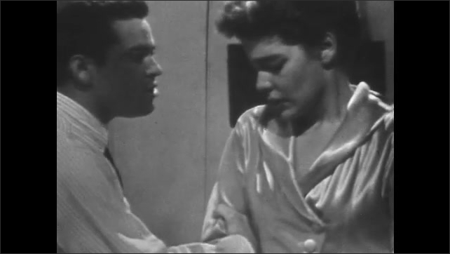 1950's: Woman walks toward window and looks out. Man grabs her arm and speaks. Woman looks away, upset.