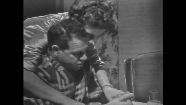 1950's: Woman in satin robe hugs man in plaid robe sitting at the table. Man shuffles cards.