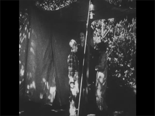 1950s: Boy and girl emerge from tent in robes. Woman comes out of tent in robe and ushers children back into tent. Boy and girl in tent, looking out.