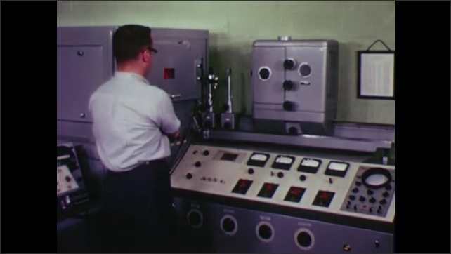 UNITED STATES: 1960s: machine in factory. Tape on machine. Man works at position on machine. Liquid pours from machine