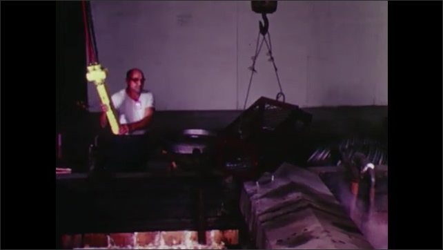 UNITED STATES: 1960s: man moves materials from flames. Machine in building