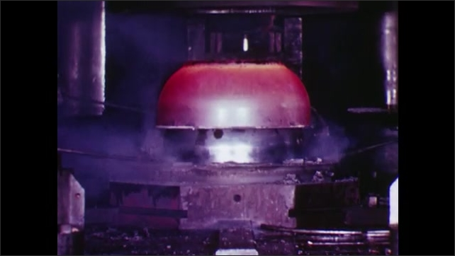UNITED STATES: 1960s: machine lifts round object from furnace. Men prepare object. Man drives vehicle to furnace