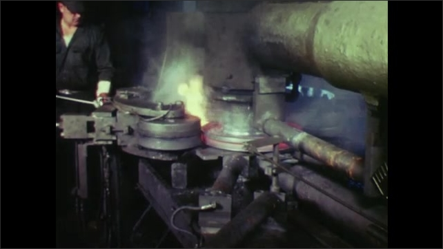 UNITED STATES: 1960s: man works with molten metal on machine. Flames around metal.