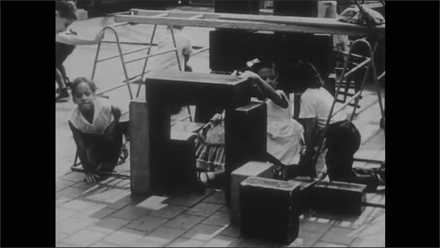 1960s: Kids playing, girl lifting block. Kids building structure with blocks. Girl crawling. Girl pats girl on back. Girl crawling.