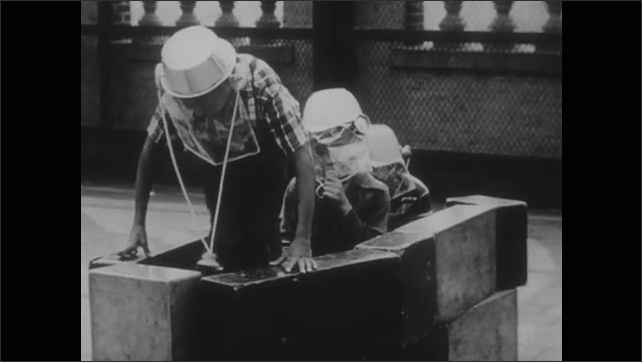 1960s: Boy sets block inside structure, sits down. Boys playing in structure with helmets.